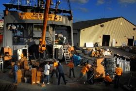 Les ministres volontaires de Scientology font une chaîne pour charger des tonnes de dons de matériel de secours sur un ancien brise-glace de la garde côtière des États-Unis affrété par l'Églisede Scientology pour transporter le personnel médical, l'équipement, les fournitures et les ministres volontaires à Haïti. Les dons comprenaient une ambulance, un camion et des fourneaux.