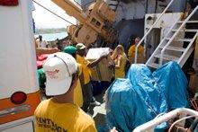 """Frivillige Hjælpere arrangerer levering af forsyninger og andre hjælpemidler, herunder """"Lifeboat for Haiti"""", som transporterede over 100 tons forsyninger fra USA til Haiti."""