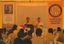 Ministros Voluntarios de Scientology Pablo y Jean Paul leyendo un mensaje enviado desde los cuarteles generales internacionales de los Ministros Voluntarios.