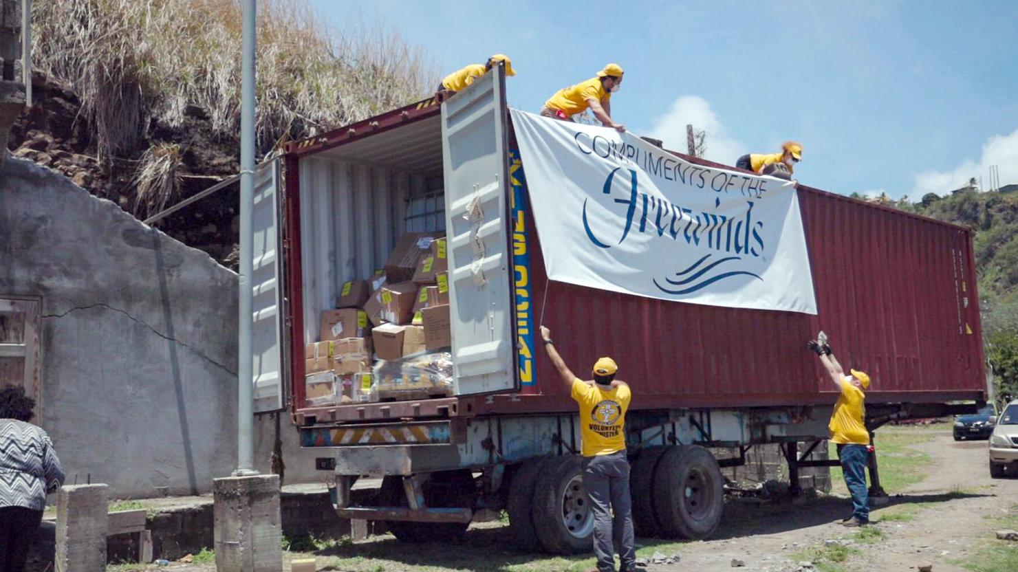 Команда саентологических волонтёров разгружает контейнер с предметами первой необходимости, которые отправил на остров корабль «Фривиндз» при поддержке МАС.