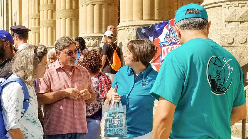 Drug-Free World stellt beim Start von Buffalos Aktivitäten zur National Night Out vor dem Rathaus Materialien zur Verfügung.