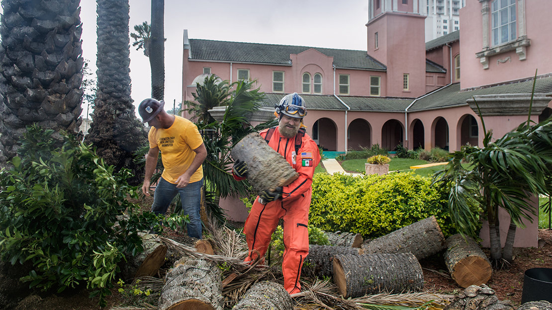 Ms and Los Topos saw up and remove uprooted trees at Peace Memorial Presbyterian Church.