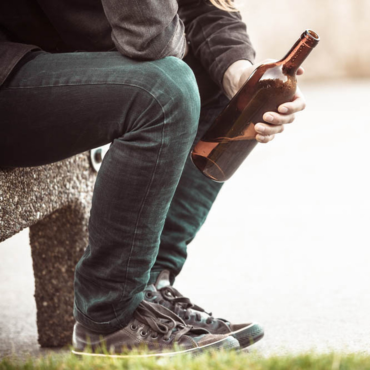 Man drinking alcohol on a bench