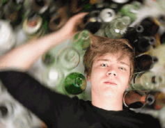 Young Man Surrounded by Bottles