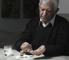 senior man taking pills