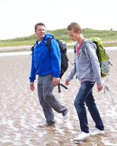 Dad and son walk on the beach as they talk.