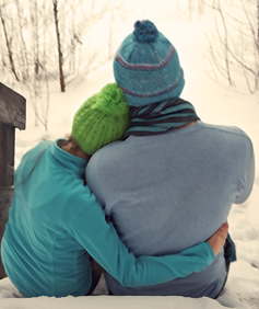 Two people hug in a winter landscape.