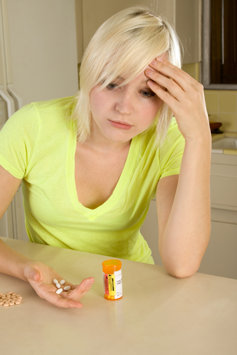 Young woman taking prescription drugs.
