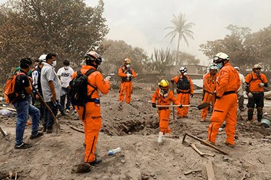 Los Topos search and rescue team dig through ashes and debris to help find missing people.