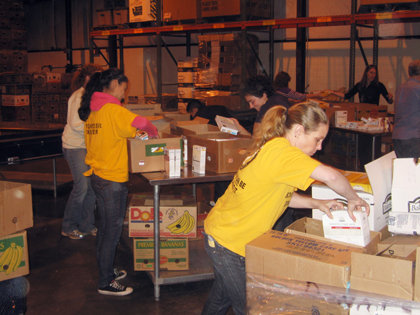 Seattle area VMs join volunteers from several local businesses and charitable organizations to pack food boxes destined for the hungry.
