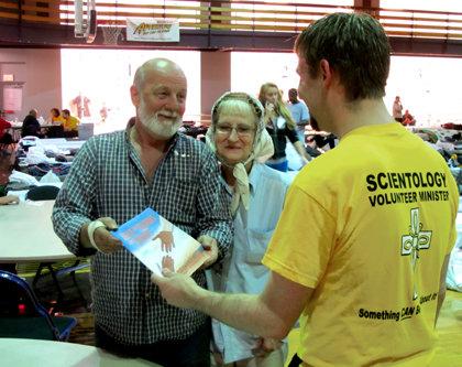 Um Ministro Voluntário ajuda um casal num abrigo.