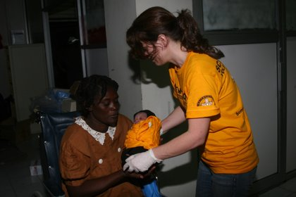 Karen handing over a newborn to her mother.