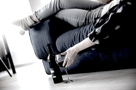 Person drinking wine at home, laying on the couch