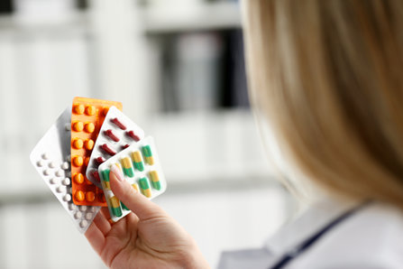 Doctor woman holding different drugs.