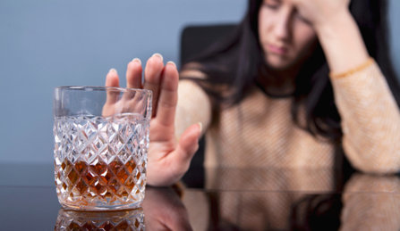 Woman refusing to drink more alcohol.