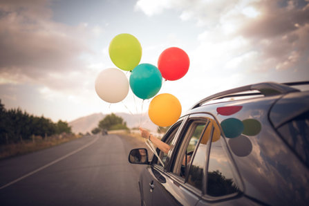 Balloons out of the window of a car