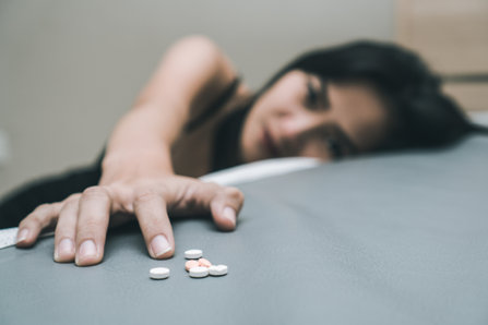 Woman reaching for pills