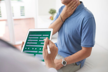 Doctor with a patient, using Prescription Monitoring System from iPad,