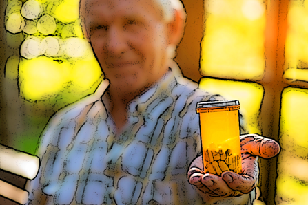 An older man holds his bottle of pills.