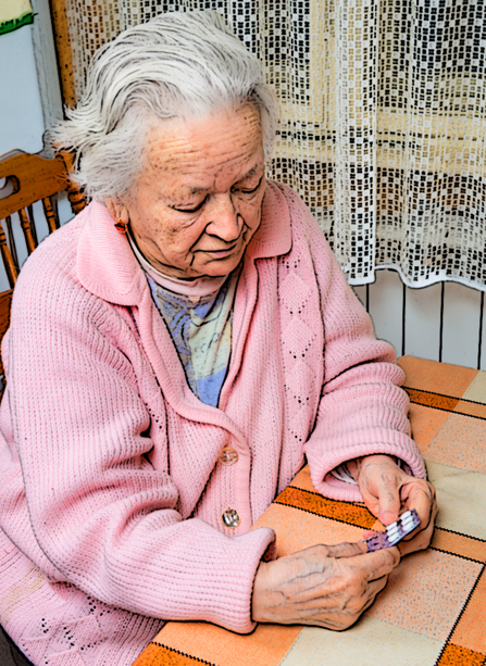 An older woman prepares to take some of the drugs she's been prescribed.
