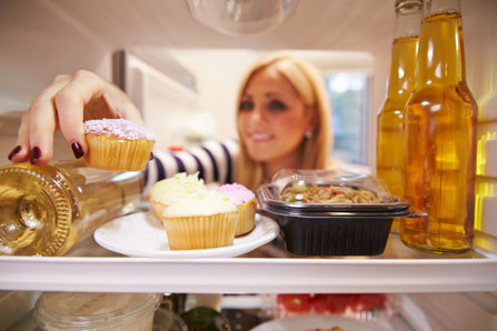 Woman takes cupcake from a fridge full of bear.