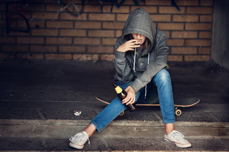 Teenager girl sitting on a skateboard, drinking and smoking.