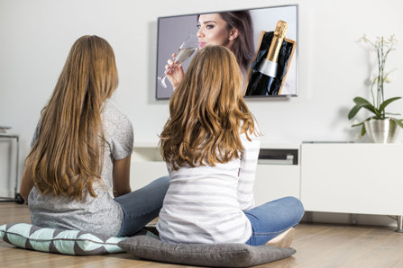 Two teenage girls are watching tv.