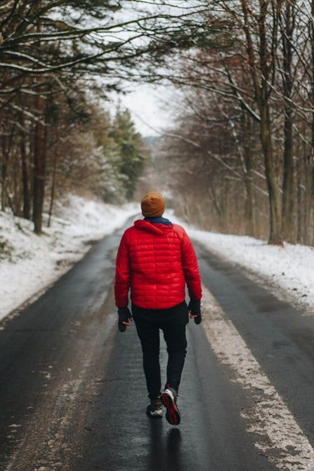 Young man walking on a snowy road