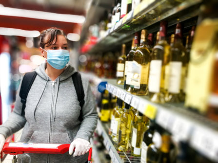 An alcoholic is shopping at store in a mask at the liquor section