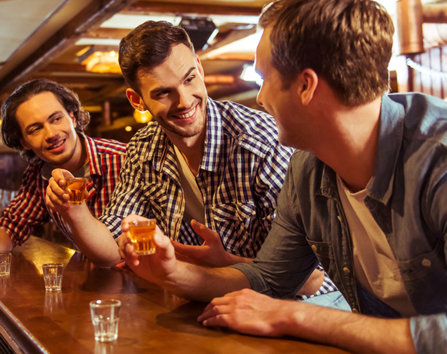 Three men drinking shots of alcohol