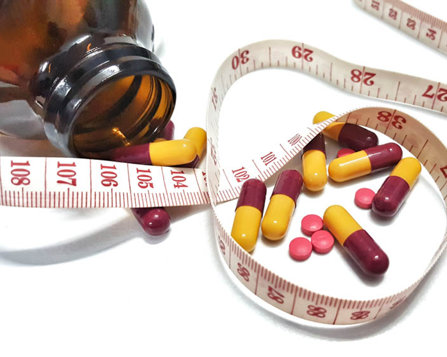 pills and a tape measure used to check weight loss