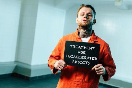 Man standing with a sign in the jail.