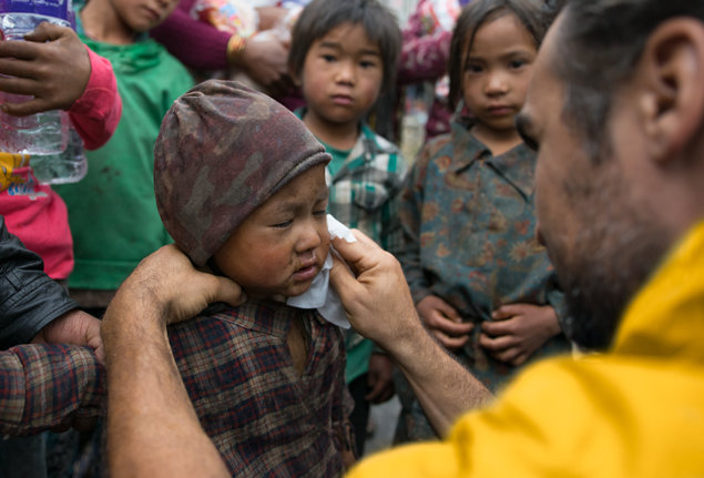Volunteer Minister from California, Mike Savas, comforts and cleans up a young boy in Nepal