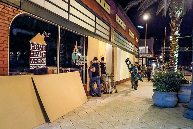 Clearwater. Scientology Volunteer Ministers putting boards on storefront