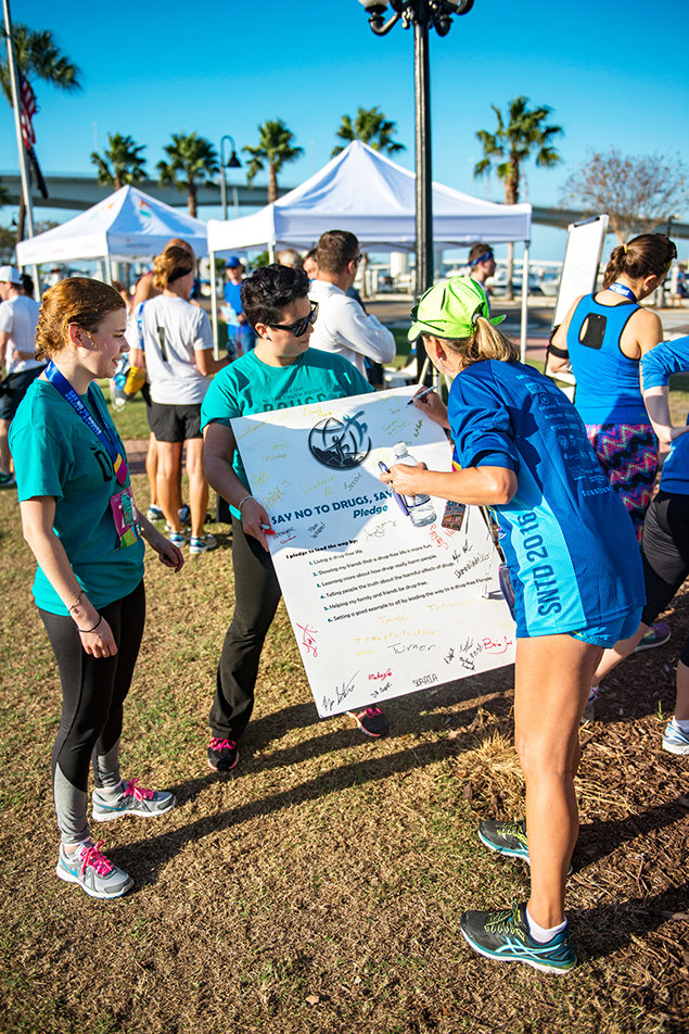 Runners converge at the 28th Annual Say No to Drugs Holiday Classic Race, where Drug-Free World distributes educational materials.