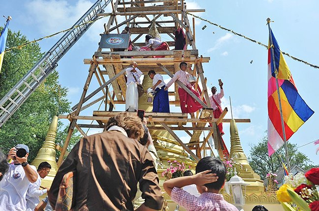 Candy and popcorn flies as the final piece of the crown is put in place at the top of the pagoda in Akron on Sunday, Aug. 26, 2018.