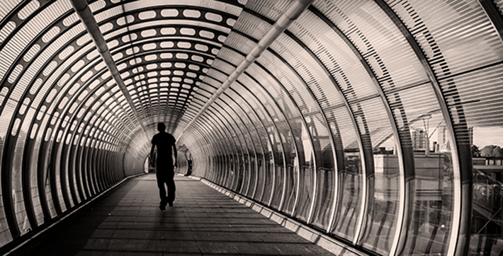 A man walks down a tunnel.