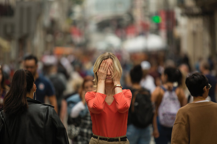 Woman covers her face in a crowd