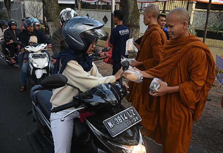 In celebration of the Vesak holiday, Buddhist monks distribute packages of sugary delicacies for breaking the fast, known locally as 'tajil', to people passing the Dammadipa Arama Vihara in Batu, Malang, East Java, on Tuesday. (JP/Aman Rochman)