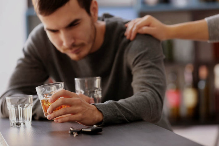 family member reaching to help an alcoholic