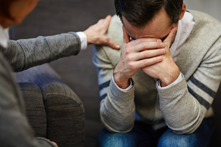 Lonely man crying during visit to psychologist