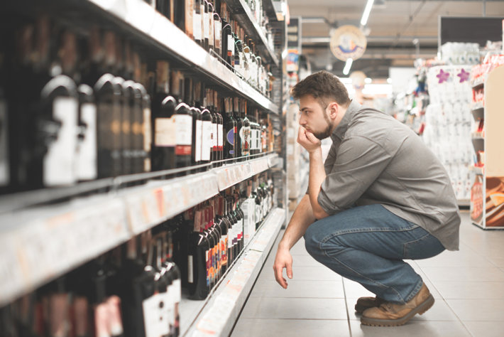 Man in alcohol section of grocery  store