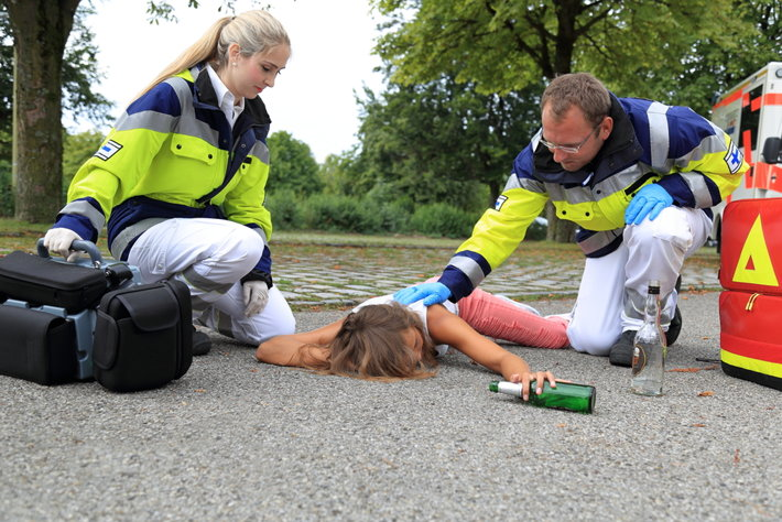 Paramedics helping a drunk woman who poisoned on tainted alcohol.