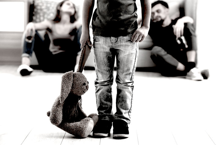 Parents addicts, child standing with a toy.
