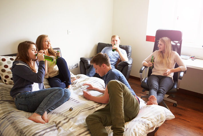 A group of teenagers is drinking alcohol in a bedroom