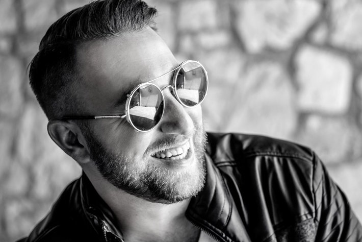 Smiling stylish man with beard and sunglasses