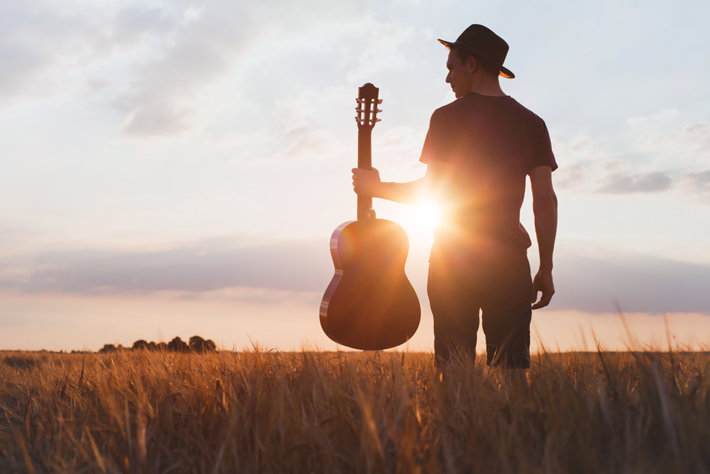 Man is standing with a guitar in a sunshine
