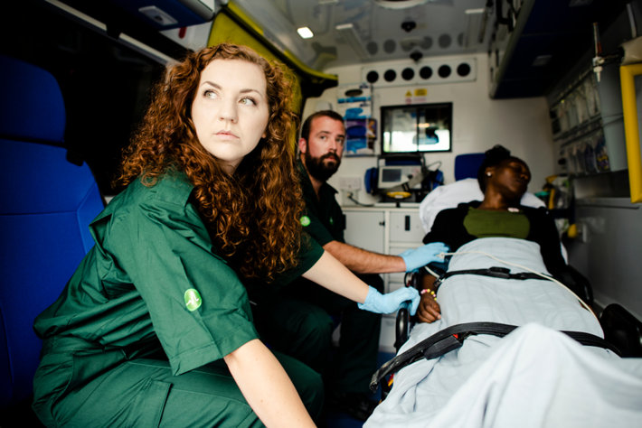 Paramedics inside ambulance car with a patient.