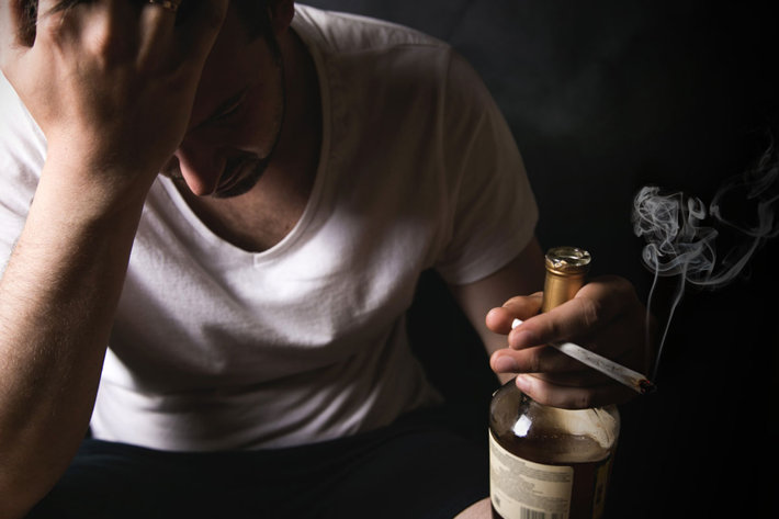 Desperate man sitting with bottle of alcohol and marijuana