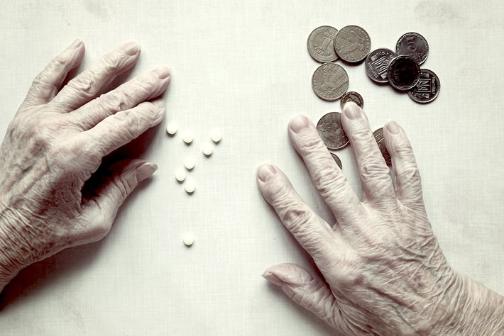 Old persons hands reaching for painkillers and money.